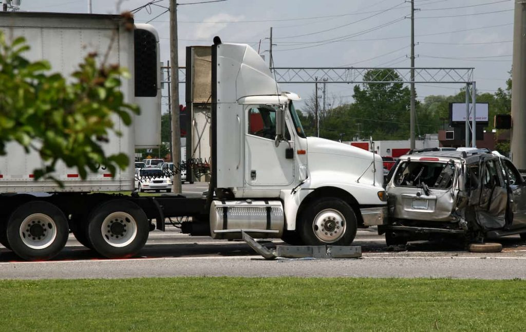 car that has been rear-ended by a semi-truck
